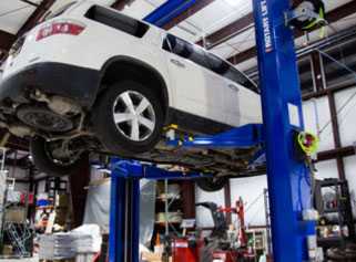 Photo of SUV on lift in the Delta Sonic Autobody and Restyling Center